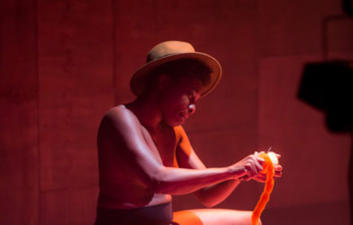 A woman bathed in pink light sits on a stage and peels oranges