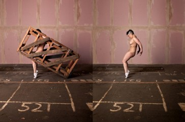 A naked women, is balancing on just her toes. Behind her is a pink tiled wall and the floor is market out with numbers. Is one side of the photo the woman is trapped in a wooden crate.