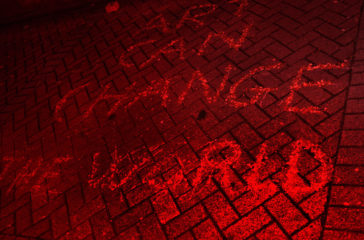 Written in chalk on the pavement, it reads 'Art Can Change The World' the photo has a red wash.
