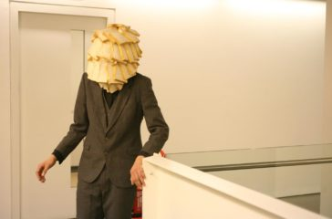 A man in a suit stands at the top of a white staircase, his face is covered in white bread.