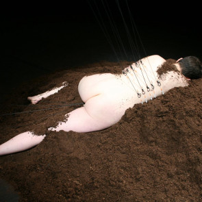 A naked man lays on a pile of soil, he has metal strings attached to his back.