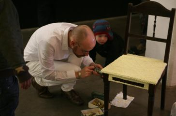 A man dressed in white, is creating a patten on a wooden chair, a toddler is watching him intrigued.