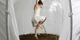 A woman dressed in white is dancing inside a white tent, the floor is covered in soil and a single bell is hanging over a stick which is stuck in the ground.