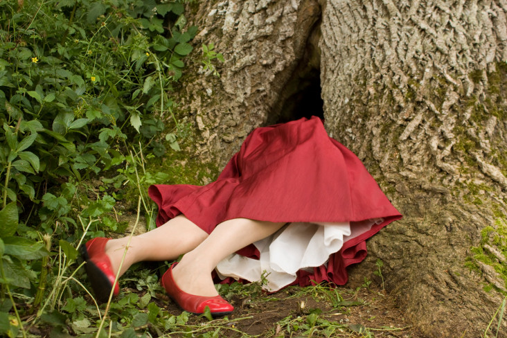 Featured News Post A woman dressed is sticking out of the bottom of a tree, she is wearing a red dress and red shoes.