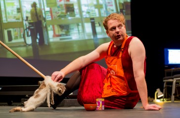 Kim Noble sits on stage wearing an apron, behind him there is a screen playing a video. He is holding a fake cat attached to a wooden poll.