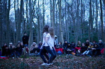 Two young girls stand in a wood back to back, a crowd of people sit around them.
