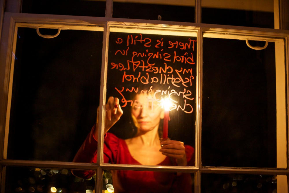 A woman is writing on a window pane, she is holding a red candle.