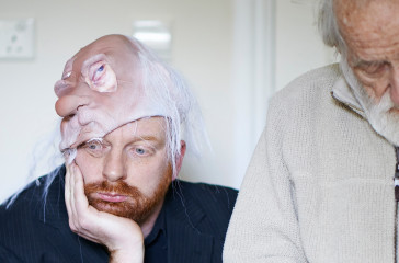 A man sits holding his face in one hand, he is half wearing a mask of an old man on his head. Next to him stands an old man looking down towards the floor.