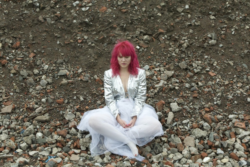 A woman with pink hair is dressed in white and silver, she is sat on the floor surrounded by rubble.