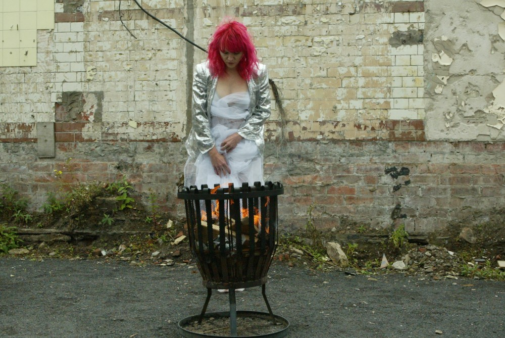 A woman with pink hair is wrapped in material, she is standing in front of a fire pit, looking into it.