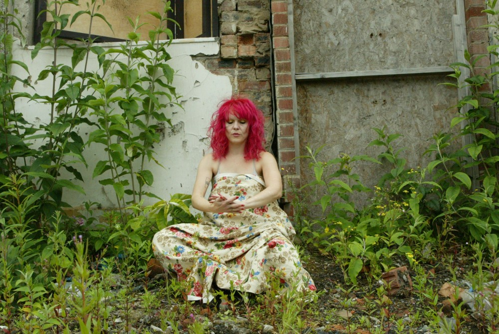 A woman with pink hair, is covered in a piece of flowery pattered material. She is knelt down in a weeded garden.