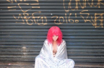 A woman wearing a pink wig and covered in a silver blanket is sat, cross legged in front of a garage door.