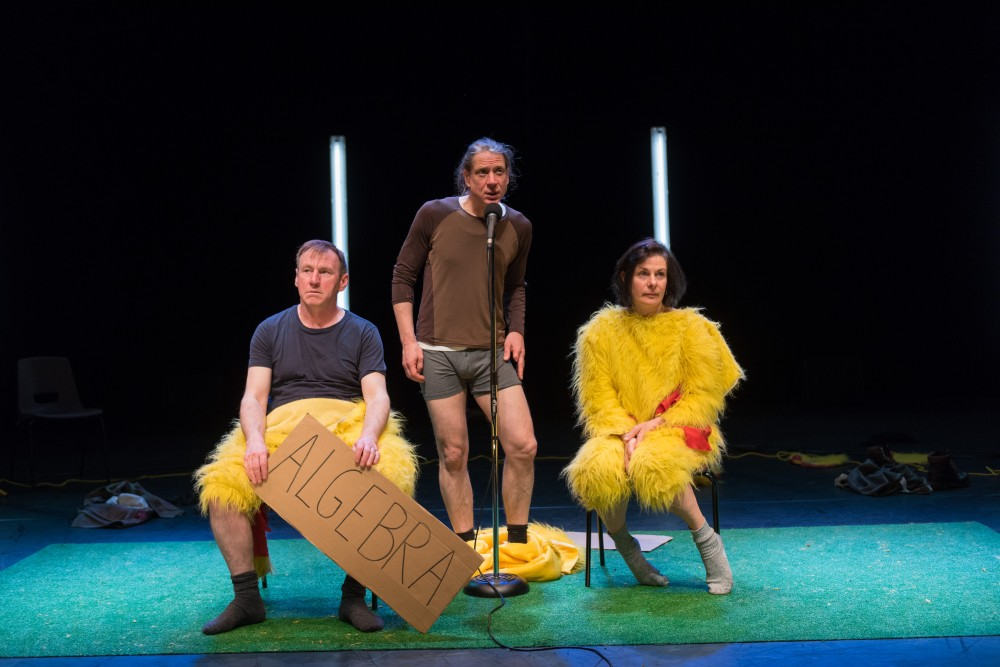 Two men and a woman are dressed in chicken suits, they are on stage in different formations.