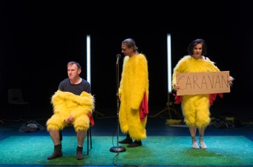 Two men and a woman are dressed in chicken suits are on a stage. One man stands in front of a microphone, one man is sat down and the woman is holding a sign that reads 'Caravan'