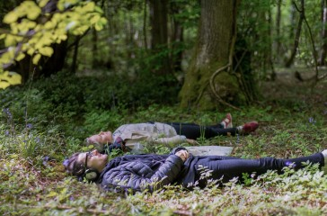 Two people lay in a woodland, they are wearing headphones they lay peacefully surrounded by trees.