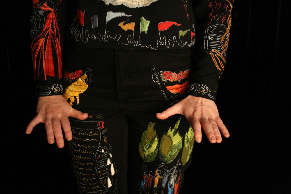 Someone dressed in vibrant colours and pattens, is stood against a black background and has their hands in front of them.