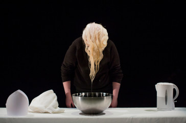 Jo has just lifted her hair out of a bowl of water, her hair drips into the bowl.