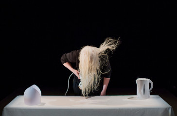 Jo Bannon is drying her hair, in front of a white table. On the table is a white object and a white kettle.