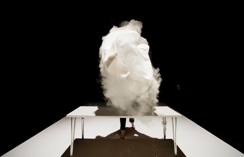 Joe Bannon is in front of a white table on stage. She has just lifted a white cloth into the air, the cloth contains white powder which has been thrown into the air.
