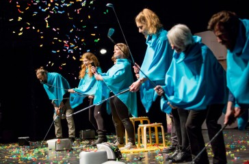 Six people stand on stage dressed in bright blue ponchos, each of them are holding a golf club, they are hitting multi coloured confetti into the air.