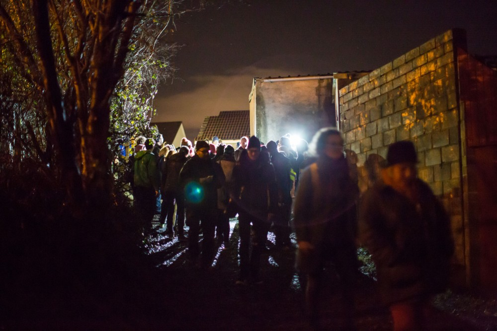 A crowd of people are walking through an ally way, the light of a torch is captured in the camera.