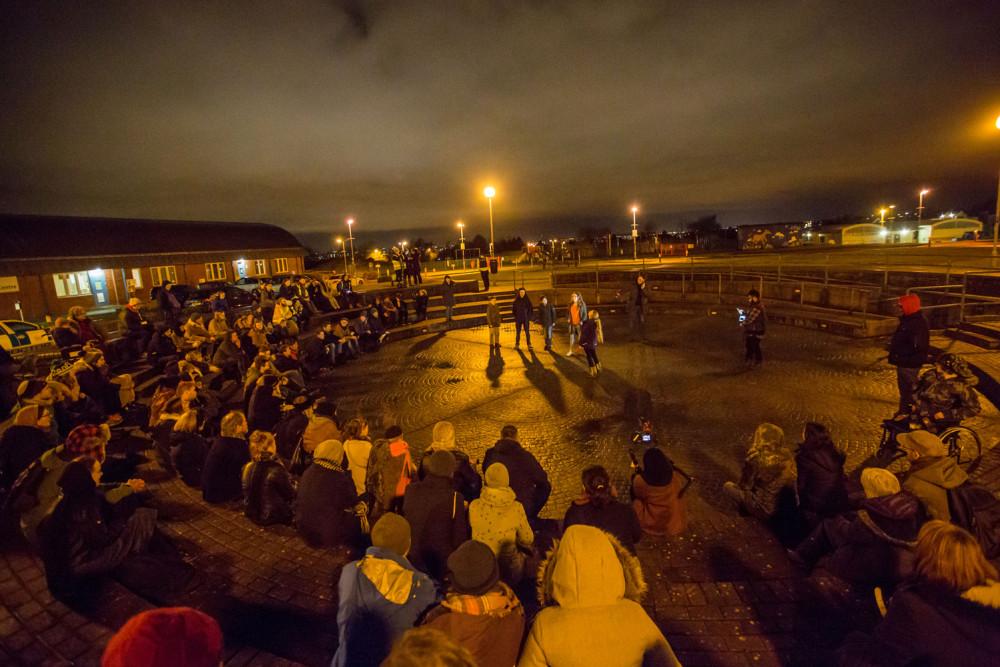 A crowd of people are standing and sitting in a outdoor arena, it is lit by street lights and six Teenagers are stood in the centre.