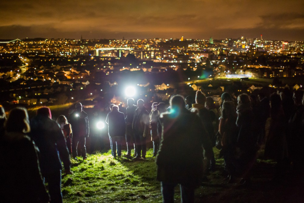 A crowd of people are stood on a hill at night, two people are shining torches towards the camera. In the background you can see the city lit up.