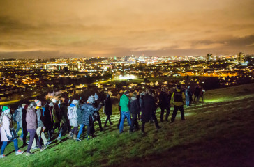 A crowd of people walk across a hill at night, in the background you can see the city lit up.