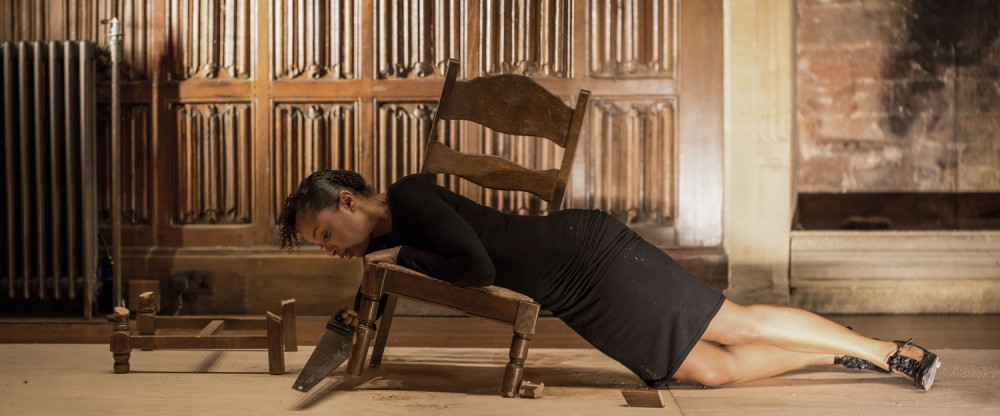 A woman is laid out on the floor, she is partially resting on a wooden broken chair, which is tilted to the side.