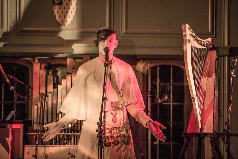Patrick Wolf stands centre stage, he is painted half black and half white and is wearing a full white costume. He stands in front of a microphone and has his arms held out and his eyes closed. He is surrounded by instruments.