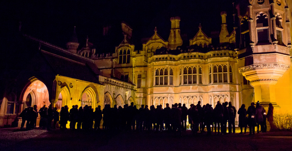 A crowd of people are silhouetted outside Tyntesfield Manor.
