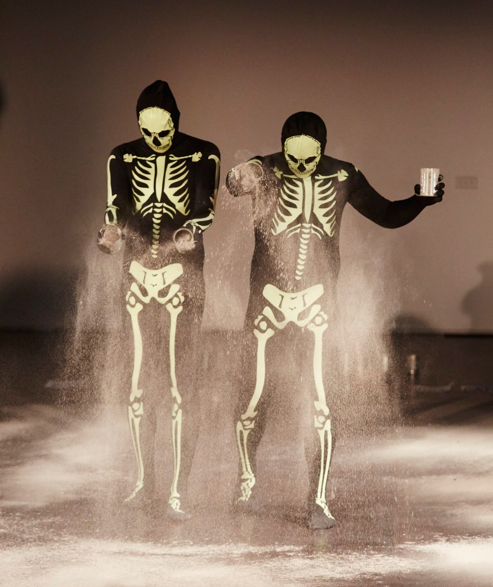 Two men are dressed in skeleton skin suits. They are sprinkling white powder onto the floor.