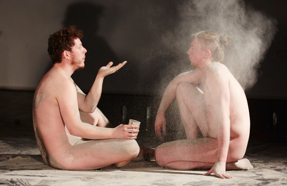 Two naked men are sat on stage, the man on left is blowing white powder into the other mans face.