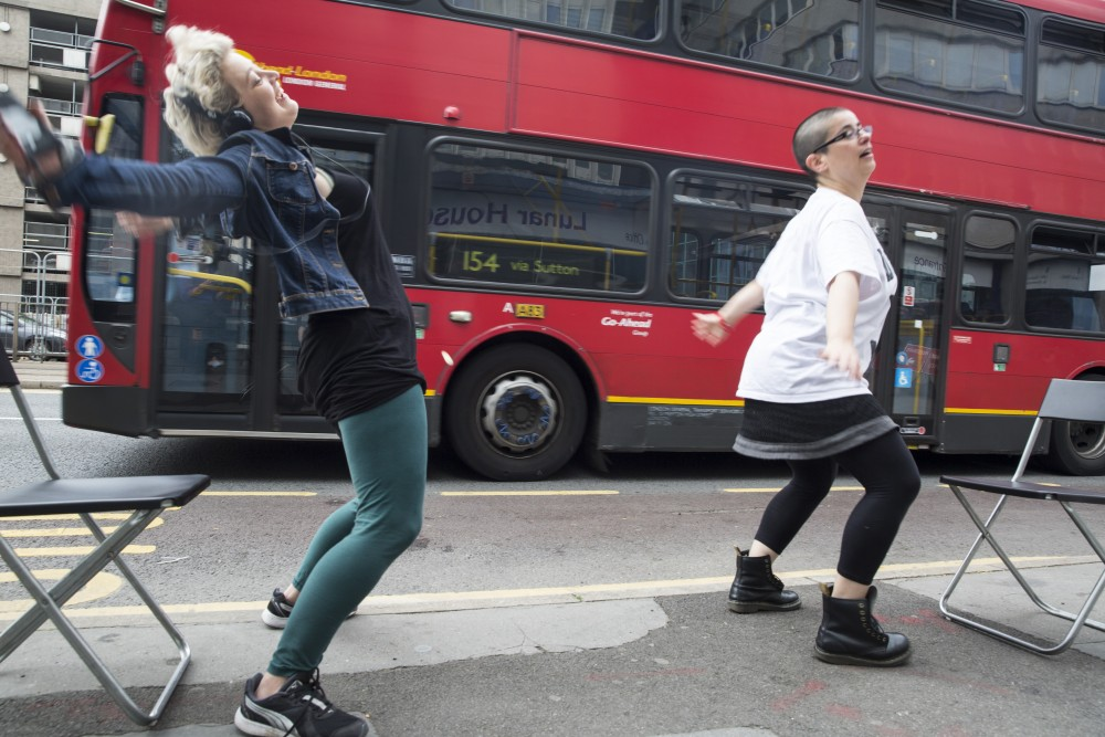 Two women are dancing in the street as a bus goes past them.
