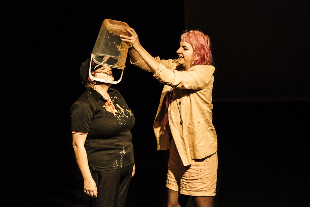 A woman with pink hair, is pouring a bucket of baked beans onto Katy Baird on stage.