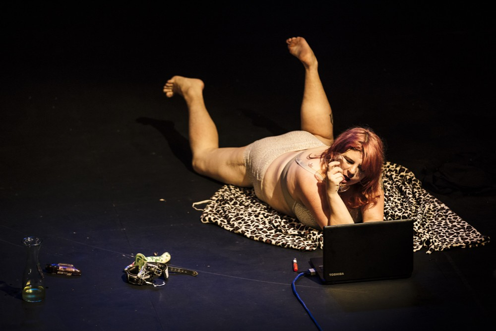 A woman lays on stage in her underwear on a leopard print blanket. She is watching something on a laptop.