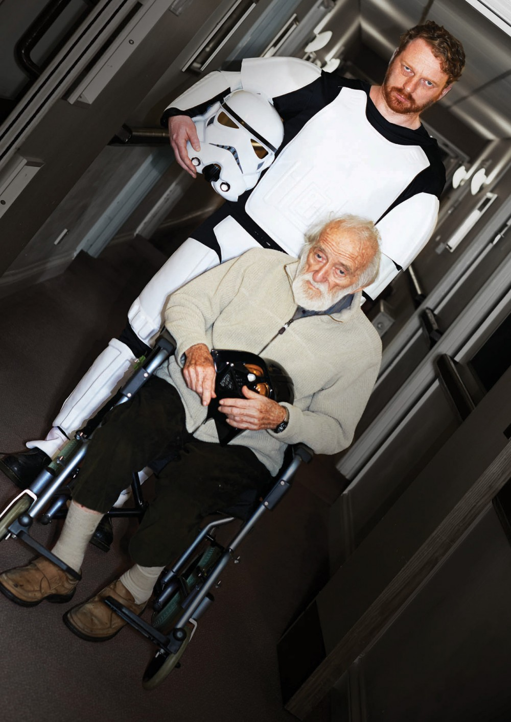 Kim Noble is dressed as a Storm Trooper, he is pushing an old man in a wheel chair towards the us.