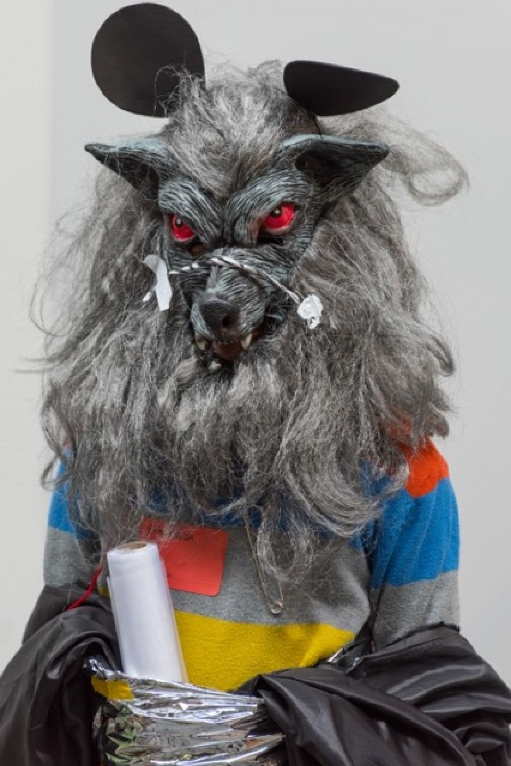 Someone wearing a stripped top and a werwolf mask is centred in the photograph. They have a role of plastic tucked into their clothing.