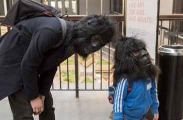 Man wearing a gorilla mask is bent over child wearing a gorilla mask.