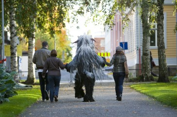 Beastie walks down a path, holding hands with a group of people.