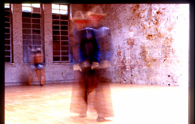A blurred image of two people dressed as cowboys in an empty warehouse.