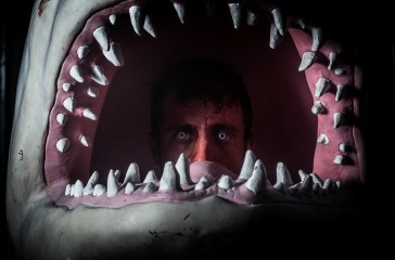 A man painted red is inside a sharks head.