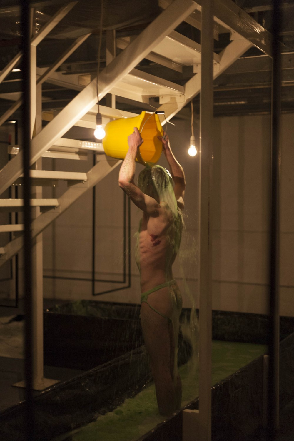 A man stands naked, holding a yellow bucket above his head. He is pouring green slim over himself.