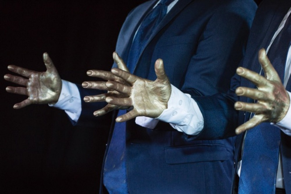 A close up of two sets of hands, painted in gold.