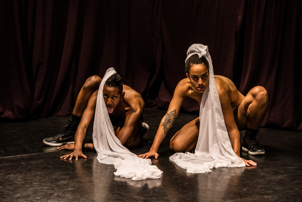 Two women are half dressed and are low on the floor, they have pieces of white material wrapped around their hair and they are strong in their pose.