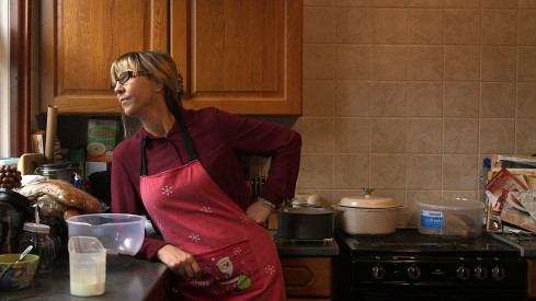 A woman stands in a kitchen, she is wearing a Christmas apron and is staring out of the window. It seems she has paused mid cooking.