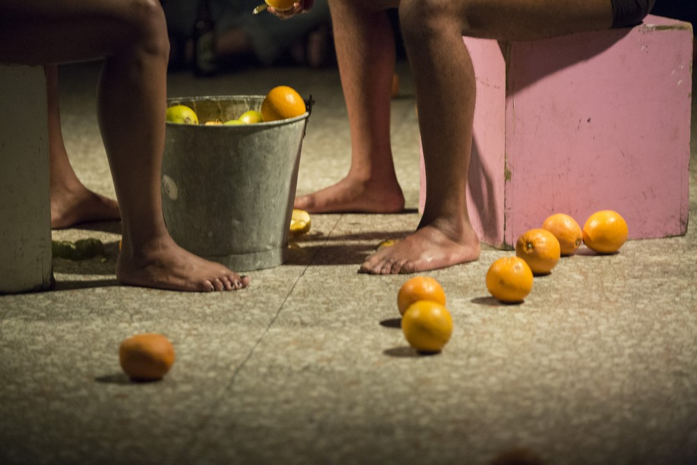 The legs of two people facing each other, with a bucket in front of them, their oranges are on the floor around them.