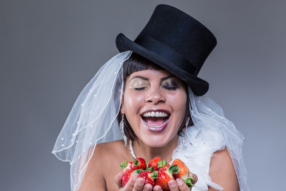 A woman laughing holding strawberries, wearingin a veil and a top hat.