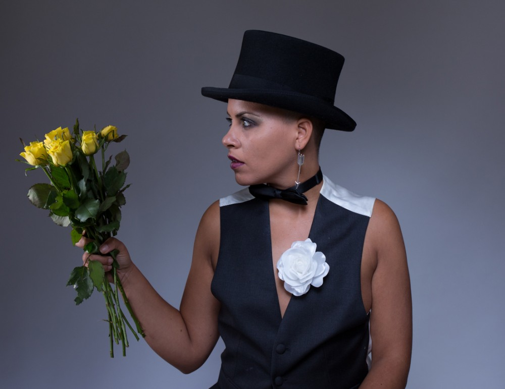 Ria is dressed in a black and white waist coat and a top hat, she is holding a bunch of flowers.
