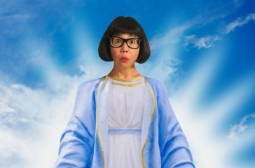 Stacy Makishi is dressed in Jesus style clothing, and is centred in the middle of a blue clouded sky.